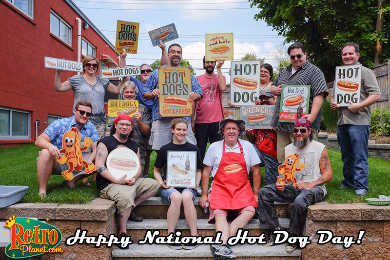 Picture of Retro Planet staff holding Hot Dog signs, wishing you a Happy National Hot Dog Day!