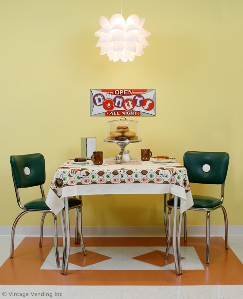 Shot of dinette set with tablecloth, tableware and retro signage.