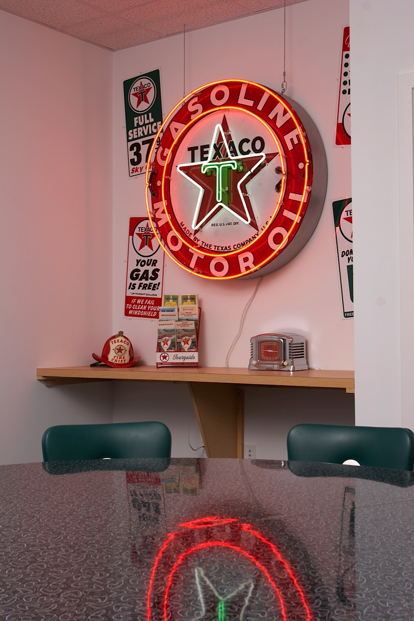 Conference room with Texaco neon sign and metal signs