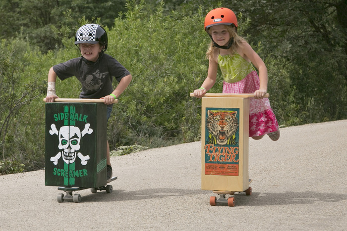 children in helmets riding Skate Crates